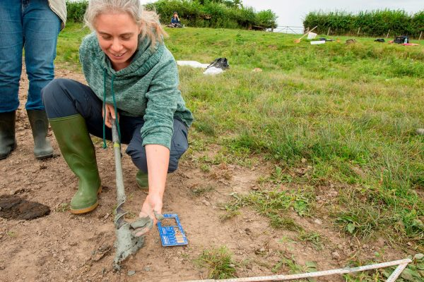 Earth Heritage Trust's Project Officer Beth Andrews examining the substrate around a pond.
